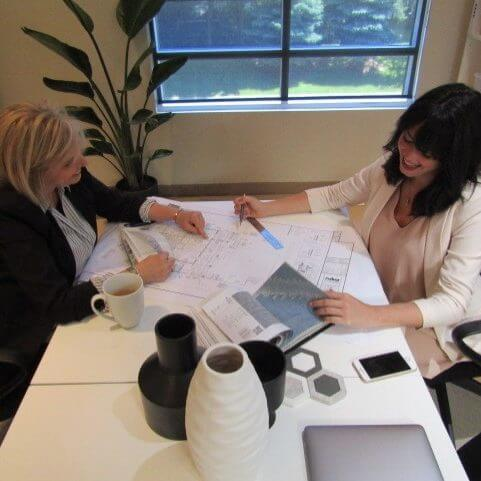 two women looking at floor plans at a white desk